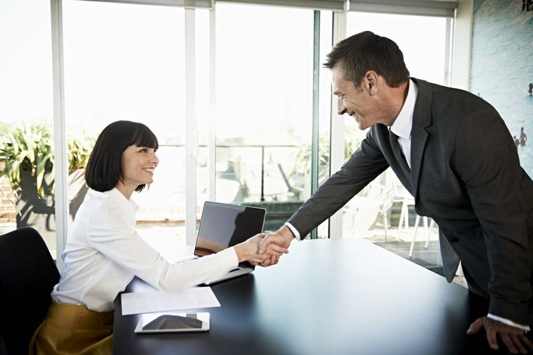 woman shaking boss' hand in office