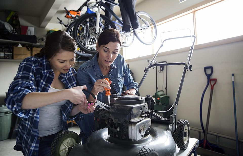 Two women fixing a gas powered lawn mower in a garage