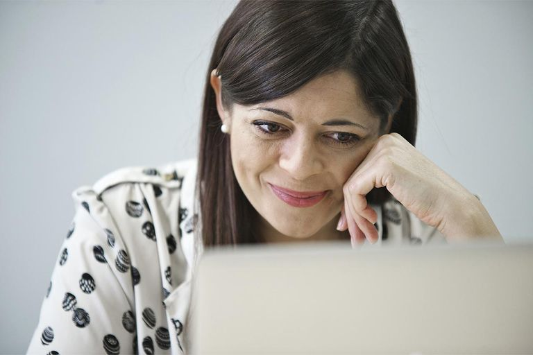 Mid adult businesswoman looking at laptop