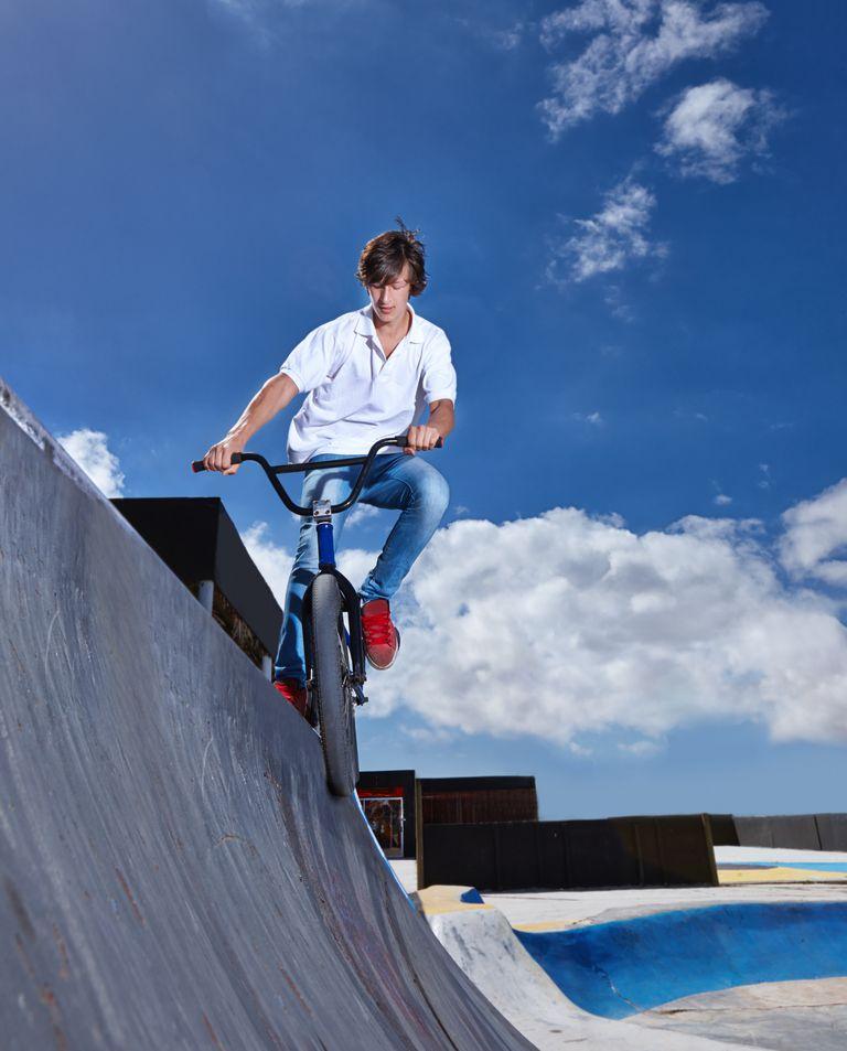 Full length shot of a teenage boy riding a BMX at a skatepark