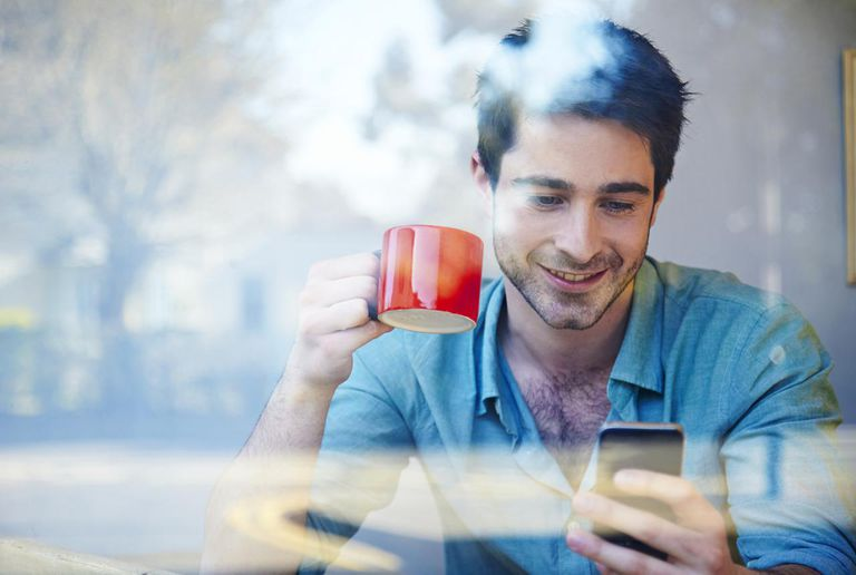 Man looking at his phone in a coffee shop window