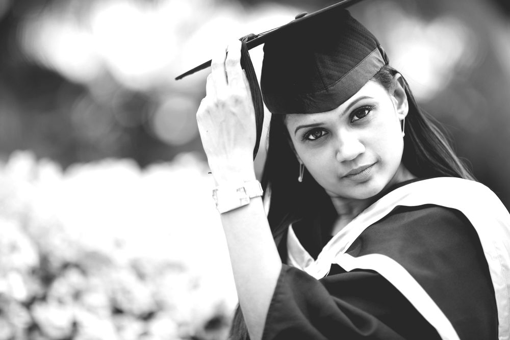 Asian woman in graduation cap, gown and stoll