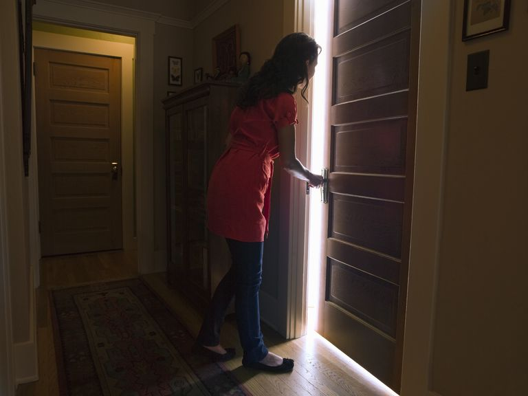 Woman opening bedroom door with light coming out
