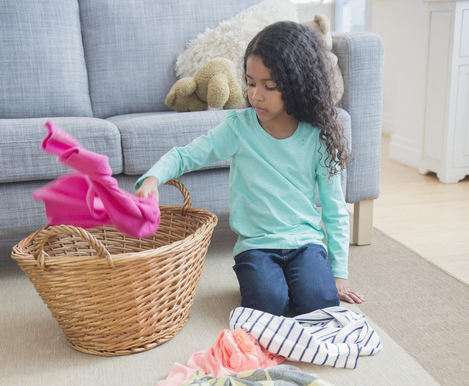 A girl places laundry in a basket.