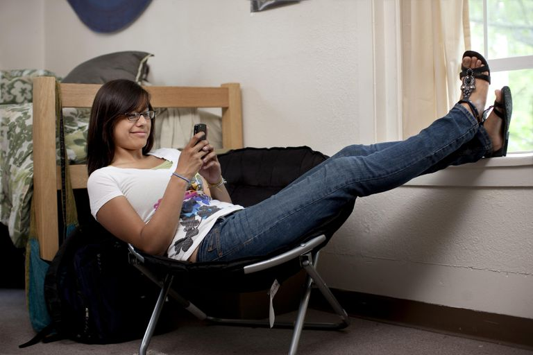 Hispanic woman hanging out in college dorm room
