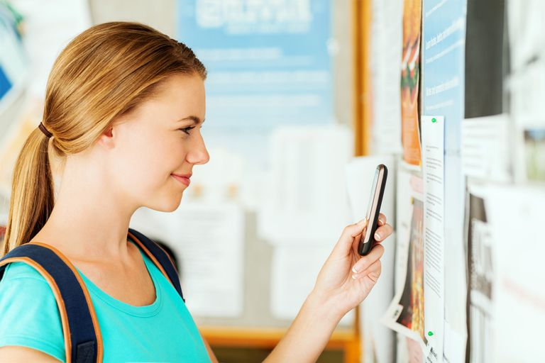 Girl Photographing Document On Bulleting Board Through Smart Phone