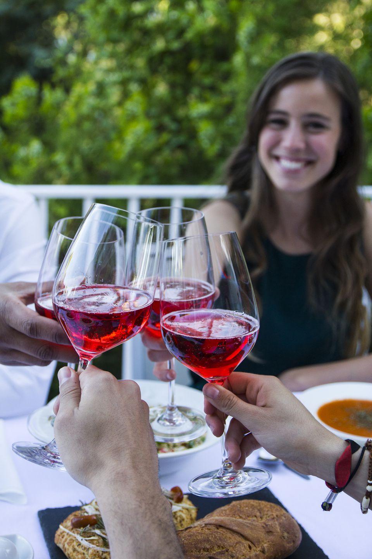 Friends enjoying Lambrusco at a summer meal