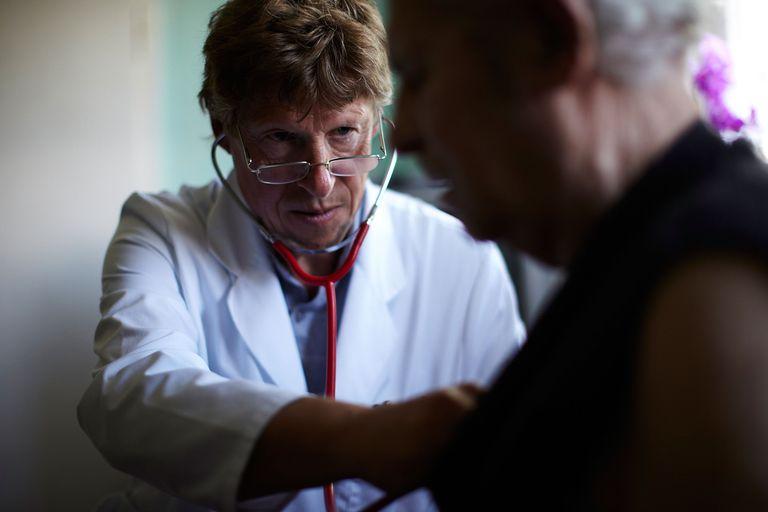 Older doctor examines patient