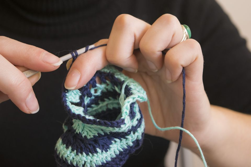 Cropped Image Of Woman Knitting Booties At Home