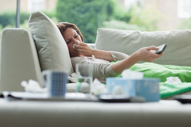 sick woman blowing nose on couch