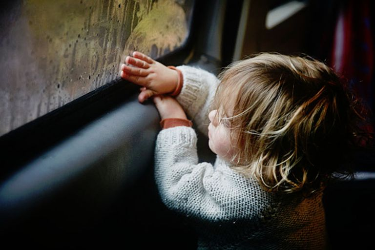 boy drawing on window condensation