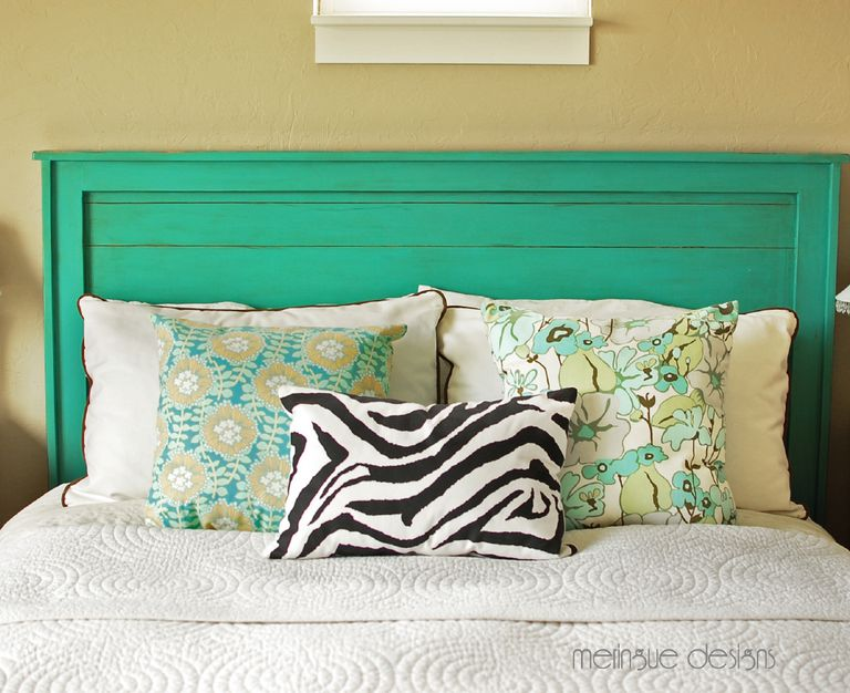 A bed with a DIY wooden headboard painted in green