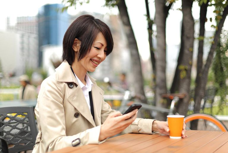 A business woman using smartphone at the cafe with bicycle