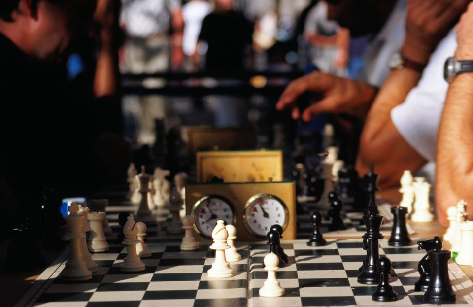 People playing chess in a table full of players