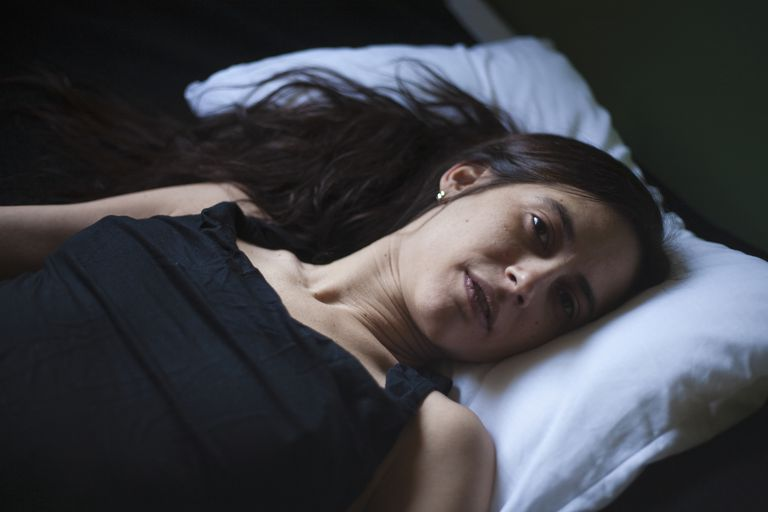 Sad mixed race woman laying in bed