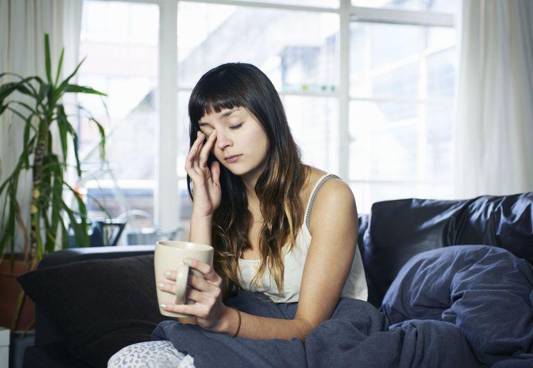 woman looking tired sitting on sofa