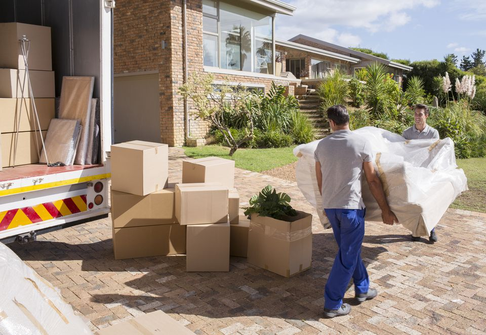 Movers carrying sofa from moving van to house