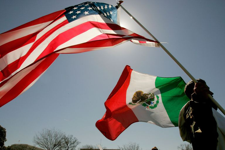 A protester holds an American flag and a Mexican flag while participating in a protest