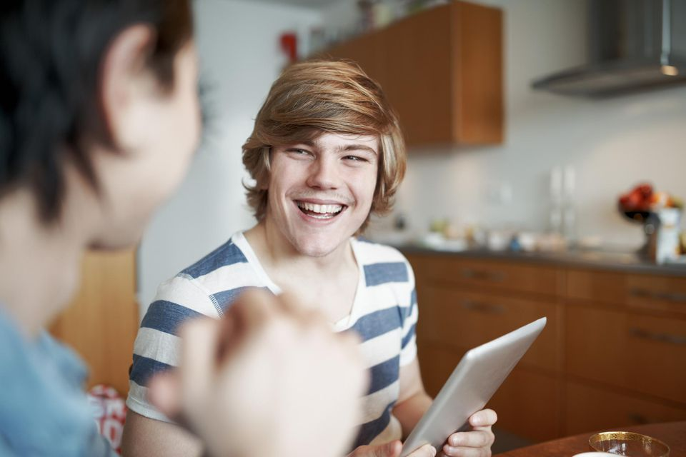 Laughing gay couple in kitchen holding a digital tablet