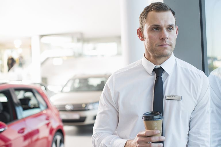 Portrait of worried salesman with takeaway coffee in car dealership