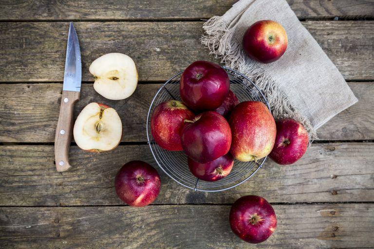 Red apples in basket on dark wood