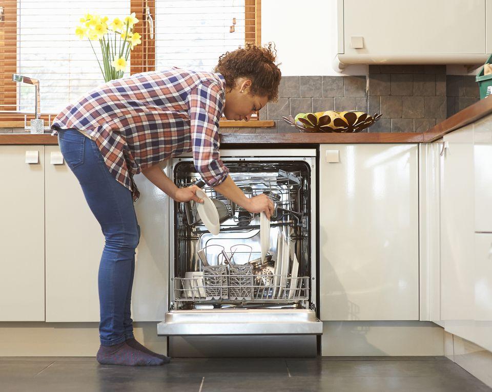 Женщина разгрузка посудомоечной машиной на кухне.
