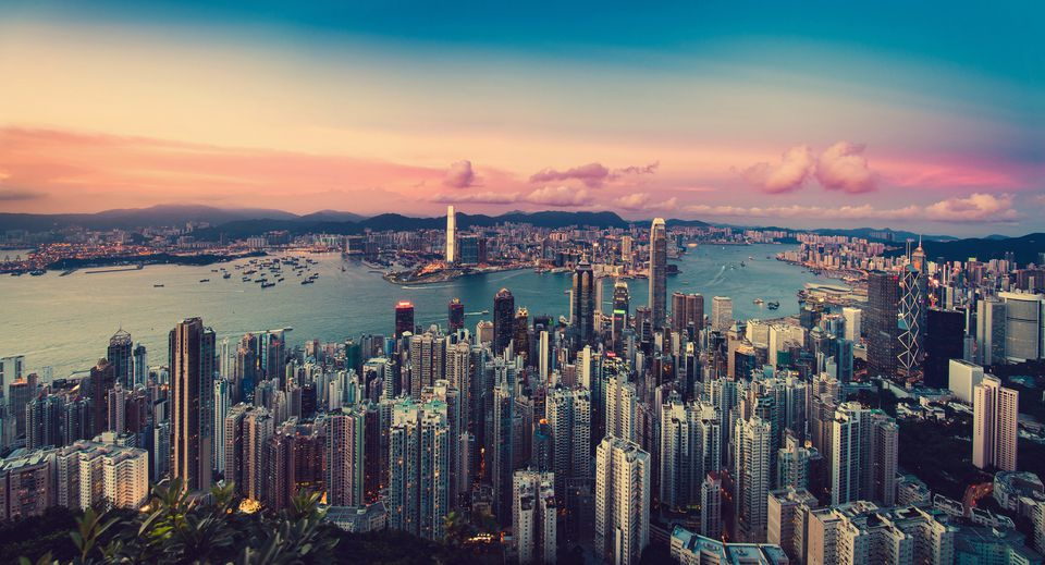 Sunset over cityscape of Kowloon Peninsula and Hong Kong Island along the Victoria Harbour.
