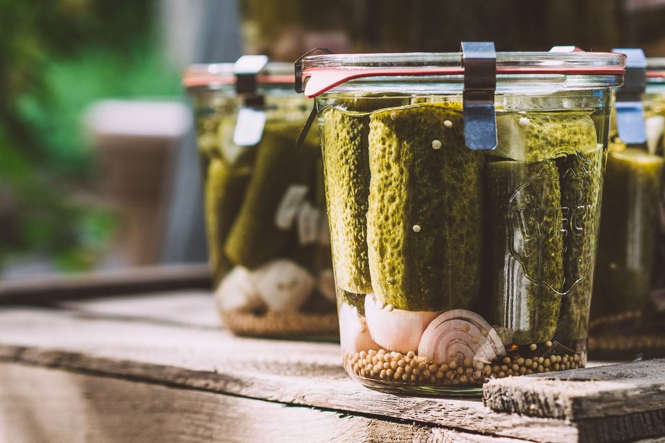 Close-Up Of Cucumber Pickle In Airtight Jars On Table
