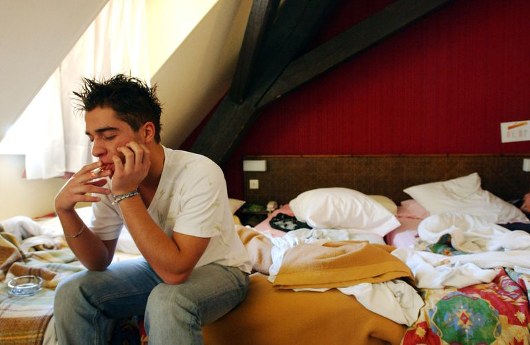 A young man smokes a cigarette on his bed and is at risk for insomnia, snoring, and sleep apnea