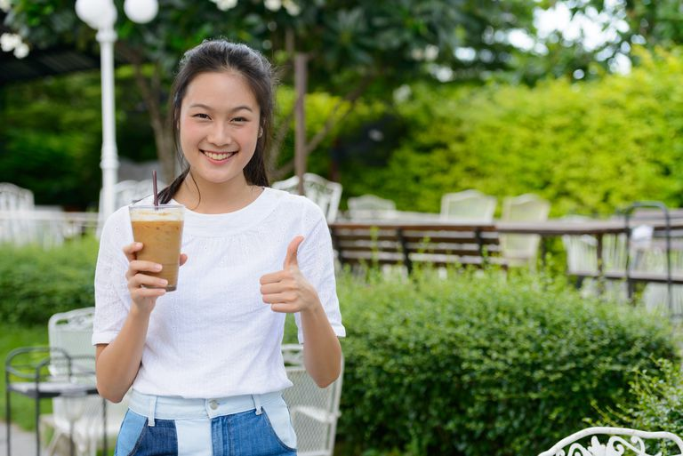 Young beautiful Asian woman holding an iced coffee and giving a thumbs up