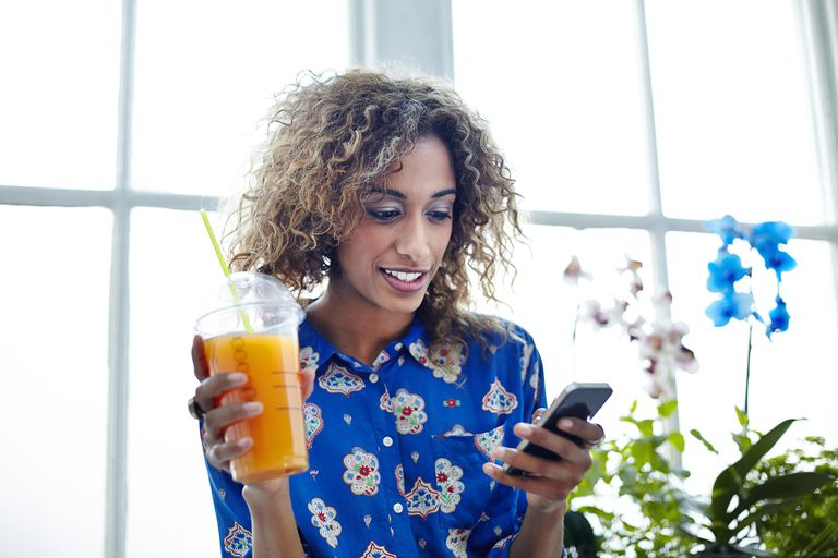 Mixed race woman drinking smoothie using her phone