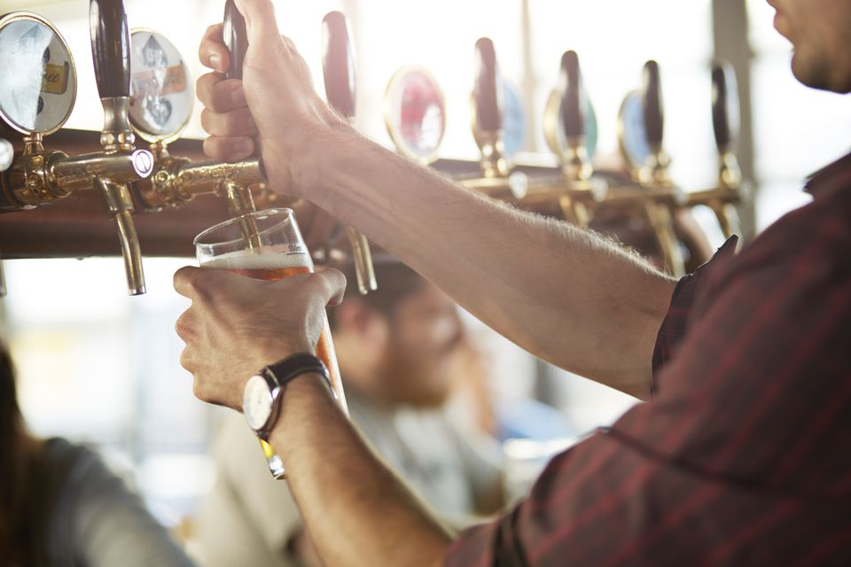 Close-up of bartender making cask beers at bar
