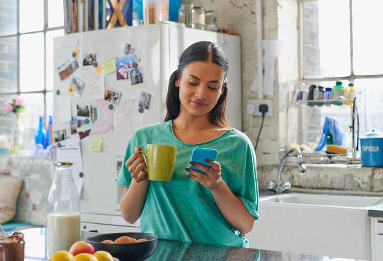 Woman using iPhone in kitchen