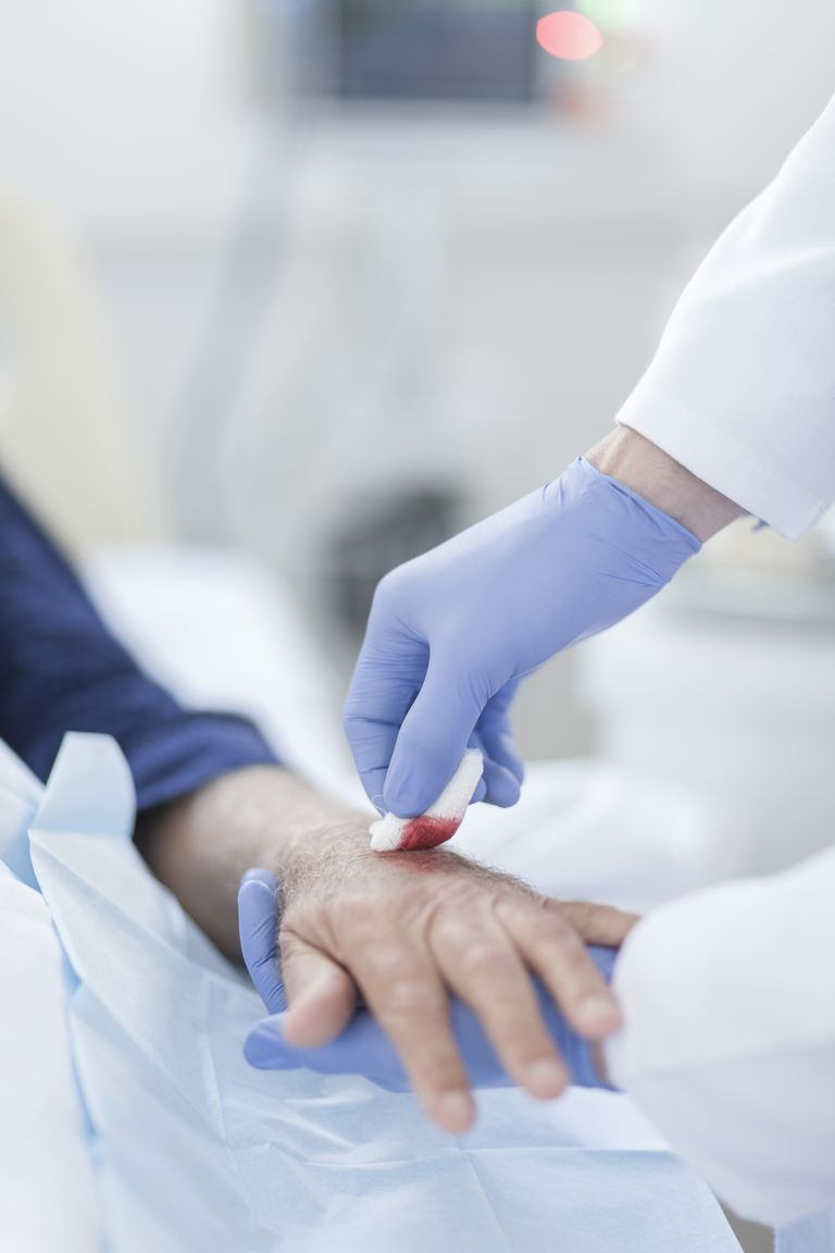 Nurse cleaning wound on patient's arm