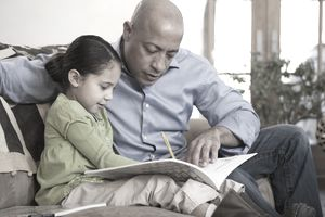 A father reading a workbook with a child