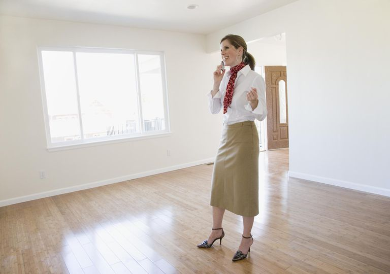 Female realtor talking on cell phone in empty house, smiling