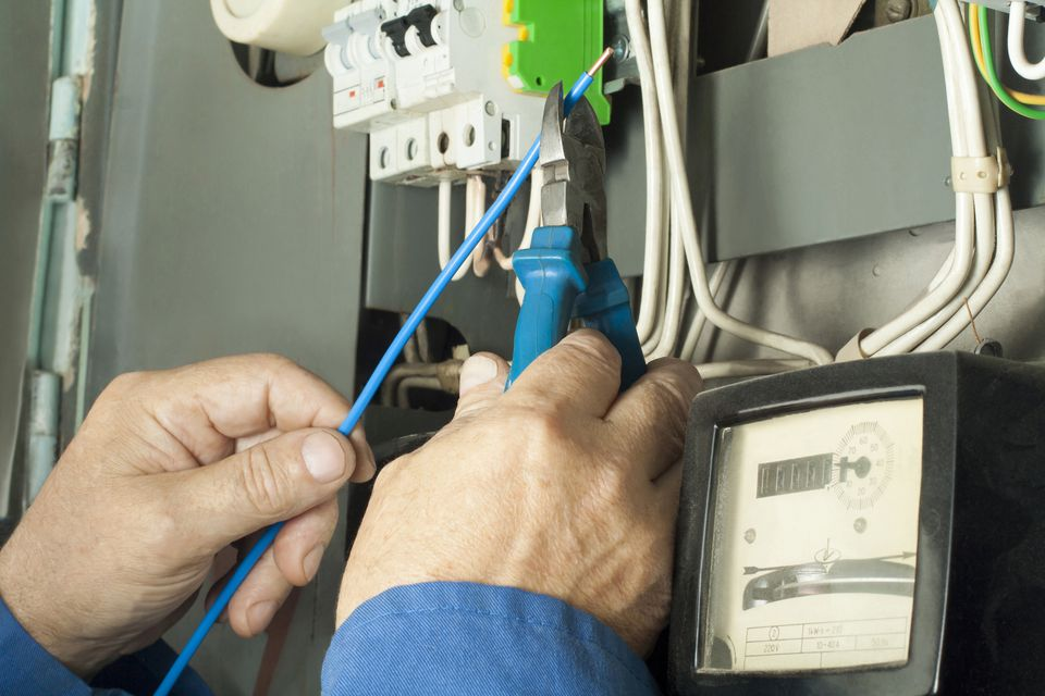 Electrician worker repairing power electrical line distribution fusebord.