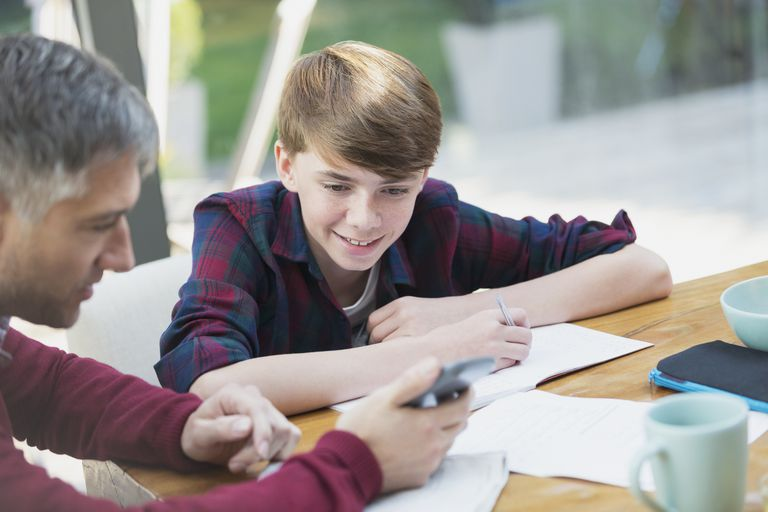 Father with calculator helping son with math homework