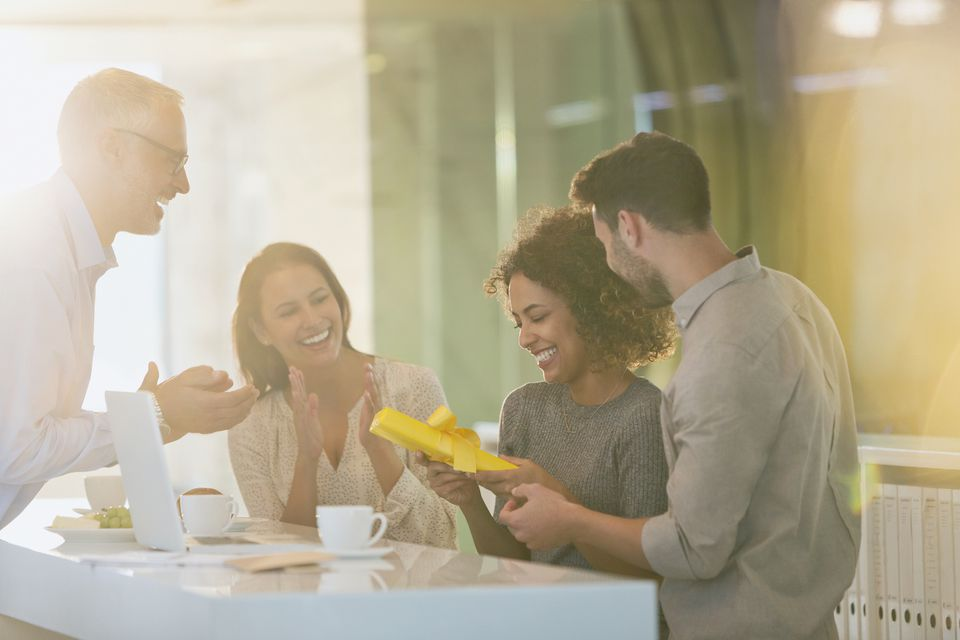 Coworkers giving businesswoman gift