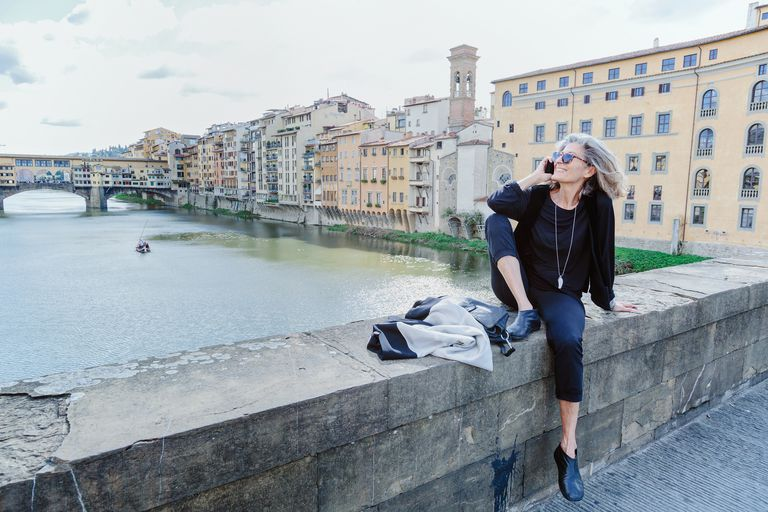 Woman sitting on Arno river bank