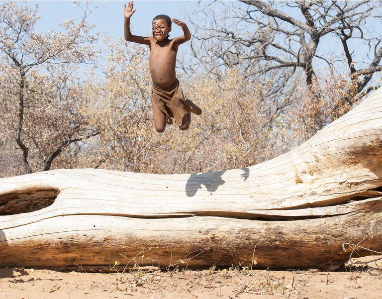 San (Bushman) child jumping of fallen tree. Grashoek, Bushmanland , Namibia