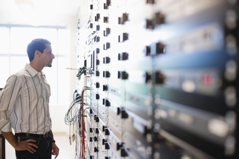 Man looking at wall of servers