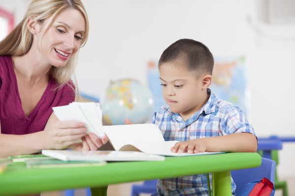 Sweet Down Syndrome boy working on flashcards with teacher