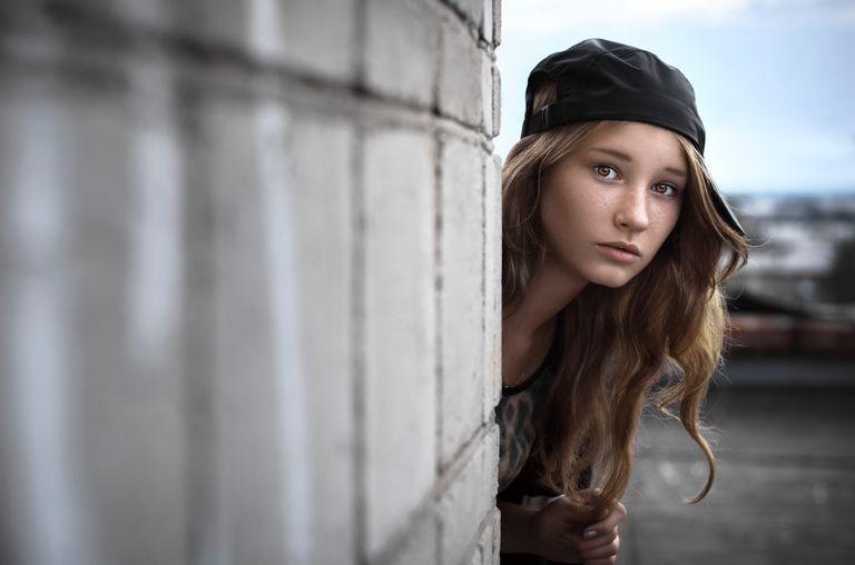 girl peeking around a corner