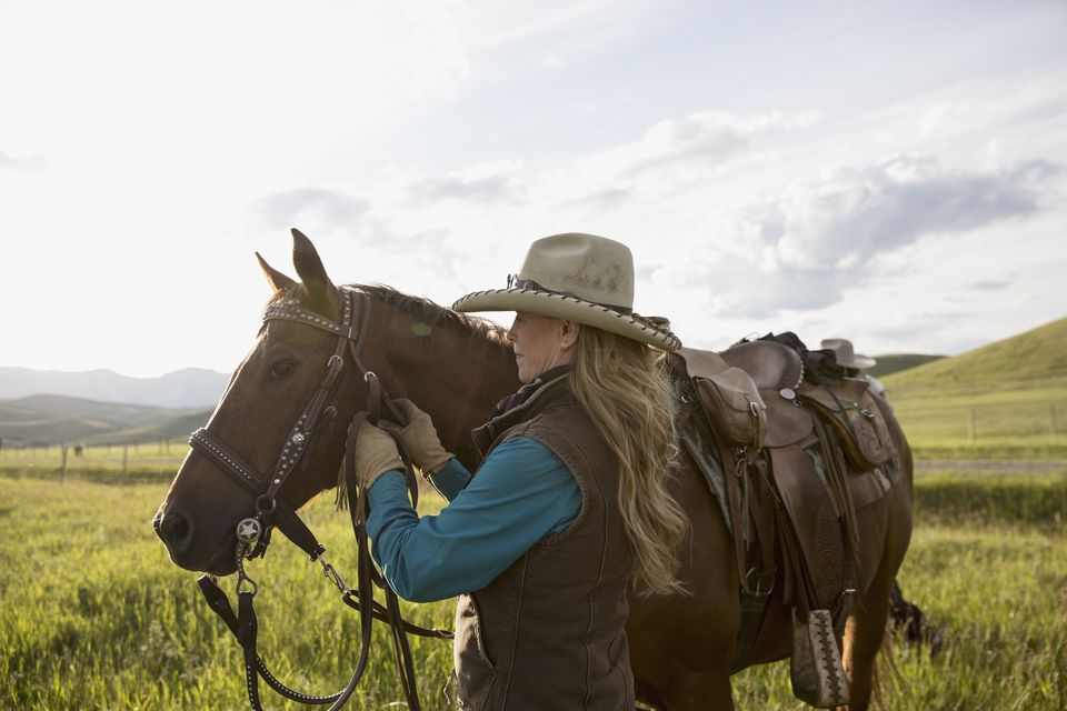 Female rancher adjusting horse bridle in field