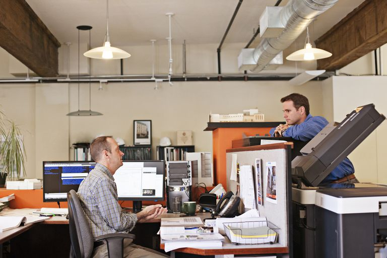 Two coworkers chat over office divide Two coworkers chat over office divide