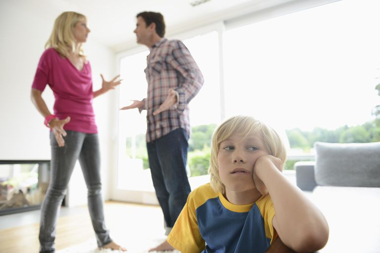 Boy looking away as parents argue behind him