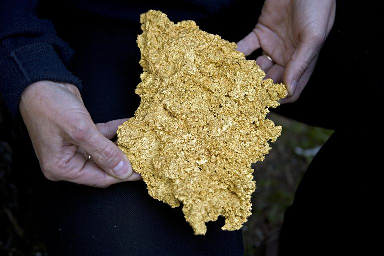 person holding large piece of raw gold