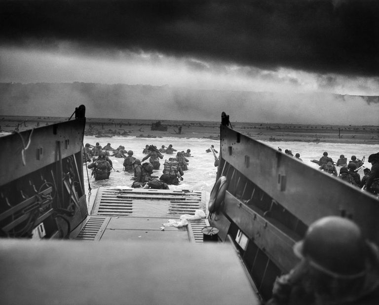 A LCVP (Landing Craft, Vehicle, Personnel) from the U.S. Coast Guard-manned USS Samuel Chase disembarks troops of Company E, 16th Infantry, 1st Infantry Division (the Big Red One) wading onto the Fox Green section of Omaha Beach (Calvados, Basse-Normandie, France) on the morning of June 6, 1944. American soldiers encountered the newly formed German 352nd Division when landing. During the initial landing two-thirds of Company E became casualties.