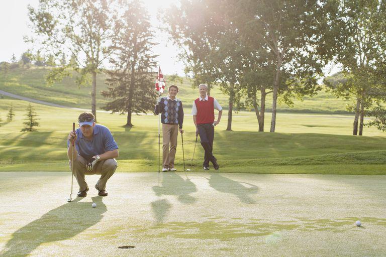 Three golfers on the putting green